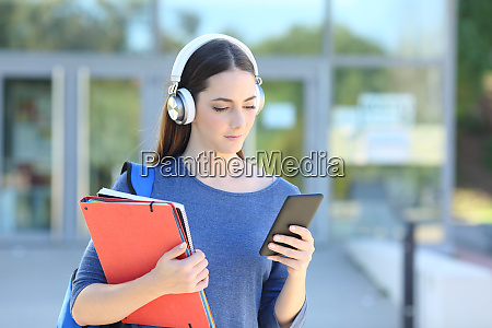 student girl wearing headset playing music