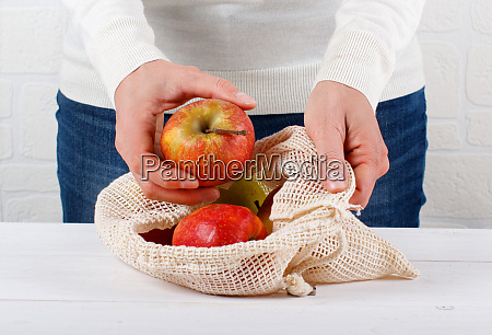 woman puts organic apples in a