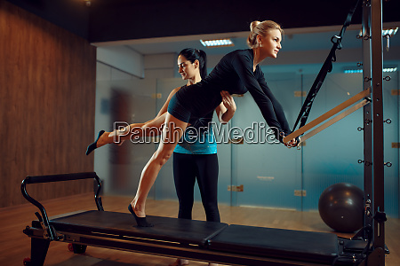 slim woman and instructor pilates training