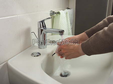 unrecognisable man washing hands