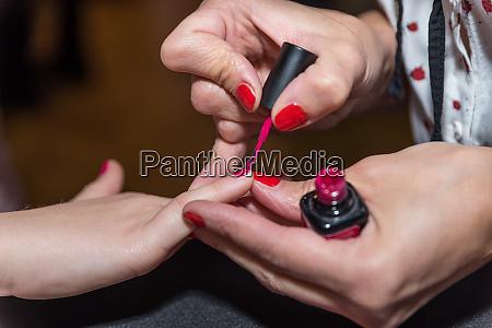 beautician paints fingernails