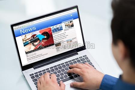 businessman reading news on laptop