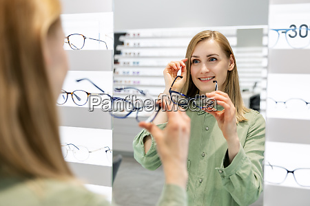 woman trying on optical glasses in