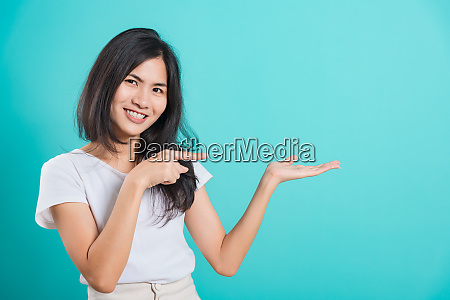 young woman standing showing hand presenting