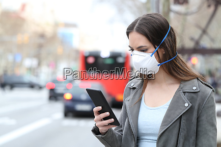 woman with mask using phone with
