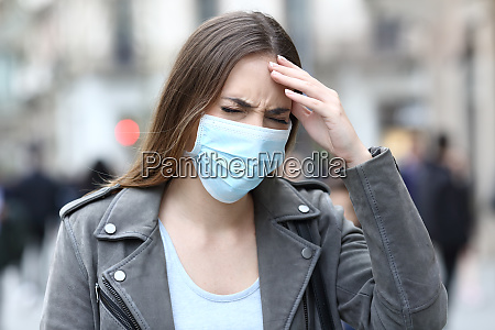 woman with protective mask suffering head