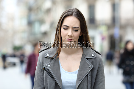 depressed young woman walking on city