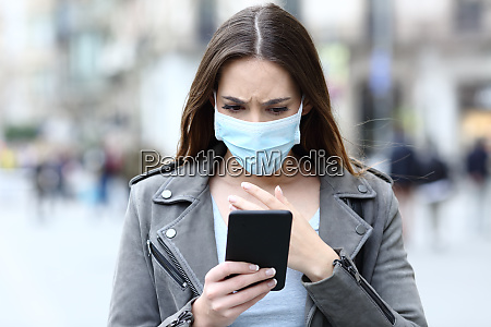 scared girl with mask reading news