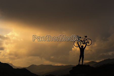 cyclist lifting bicycle against sunset on