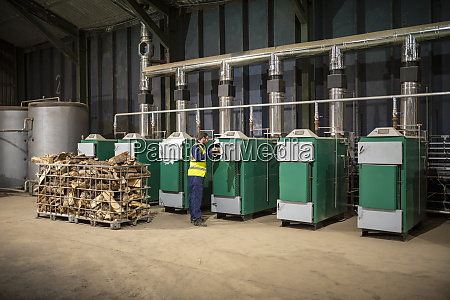 worker filling furnaces with wood to