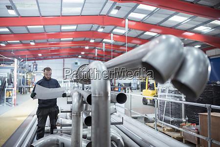 engineer inspecting drawings of tubing in