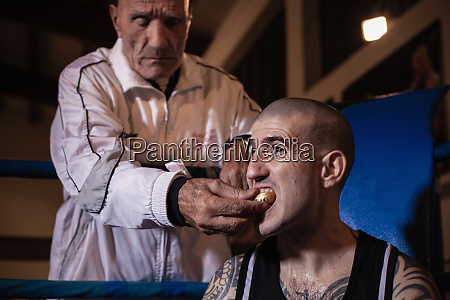 boxing coach removing mouth guard from