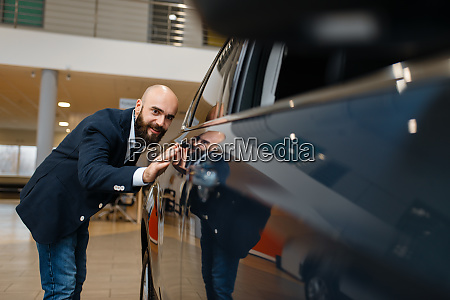 man checks the paintwork of new