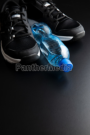 black sport shoes and bottle of