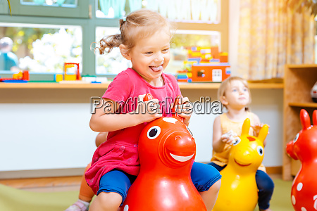 little girls riding on play horses