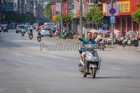 older man riding on a scooter