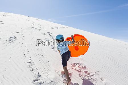 a young boy climbing sand dune