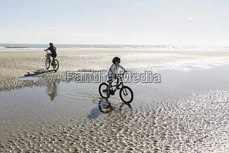 two children cycling on an open