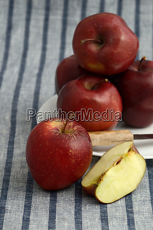 delicious apples in plate with knife