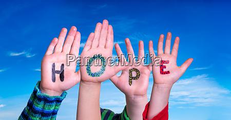 children hands building word hope blue