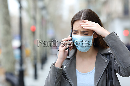 worried woman with protective mask calling
