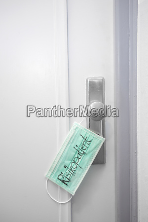 medical mask on apartment door with
