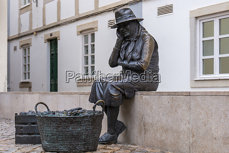bronze statue of old saleswoman