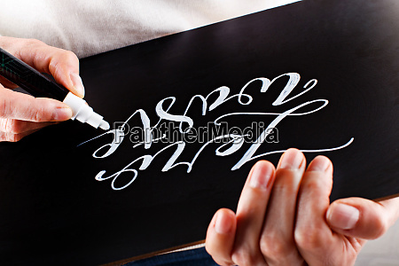 woman writing on a small chalkboard