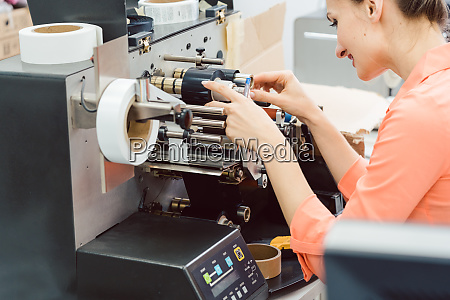 woman working on label printing machine