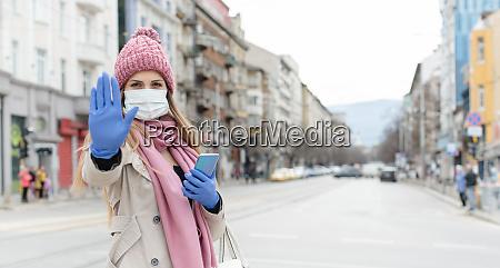 woman wearing corona mask giving stop