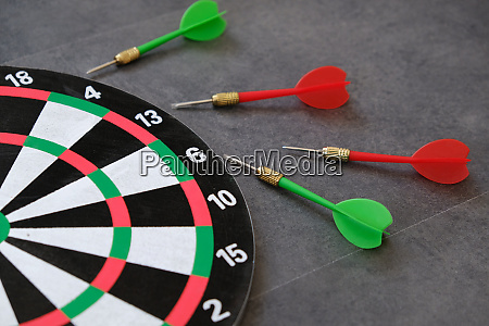 dartboard and dart arrows standing on