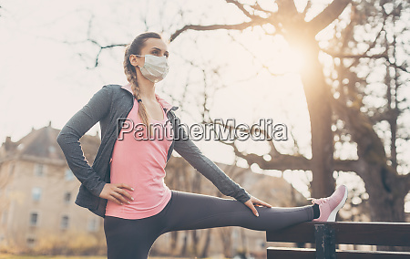 woman wearing face mask stretching on