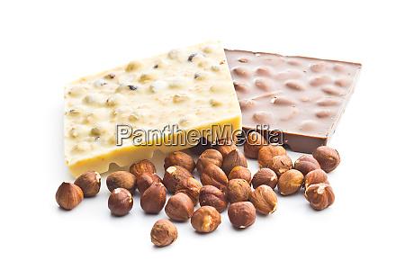 chocolate bar and hazelnuts on white