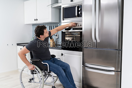 disabled, man, using, microwave, oven, in - 28215140
