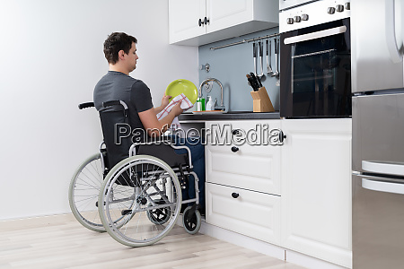 handicapped, man, cleaning, dishes, in, kitchen - 28215139