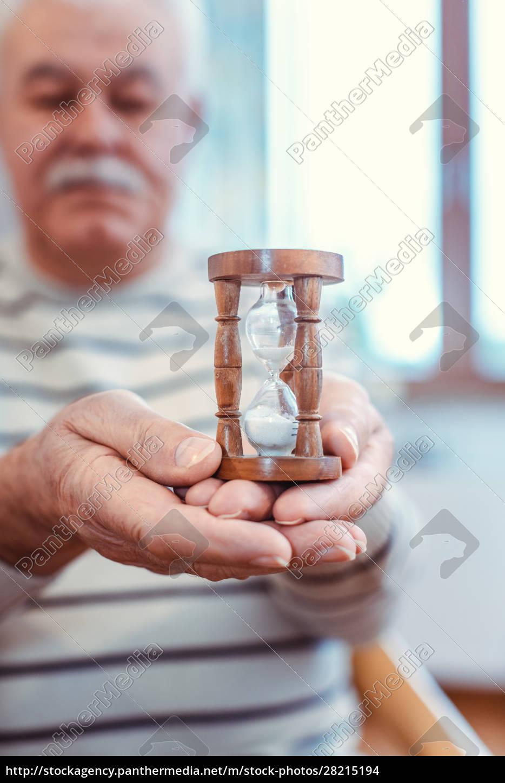 senior, man, holding, hourglass, in, retirement - 28215194