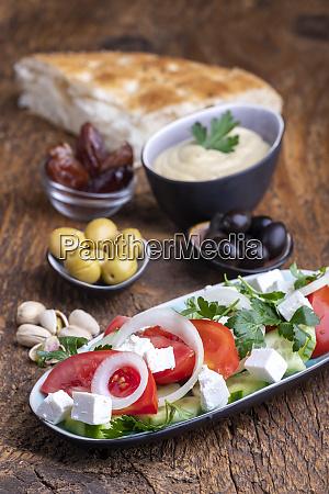 olives and hummus on dark wood