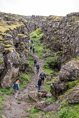 tourists walk through the almannagja fault