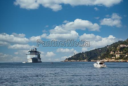 yacht approaching white cruise ship