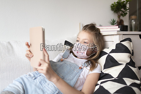 young girl with pink protective mask