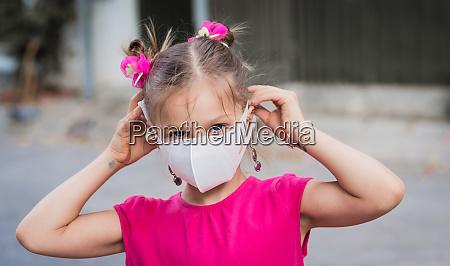 girl wearing facial disposable mask virus