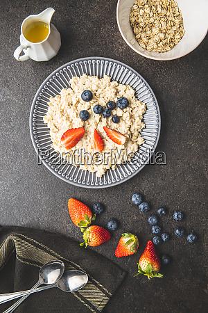 plate of oatmeal porridge with strawberries