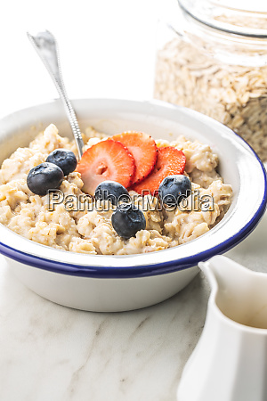 bowl of oatmeal porridge with strawberries