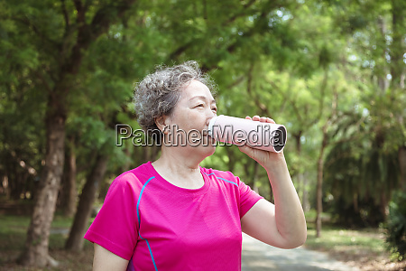 asian senior woman drinking water after