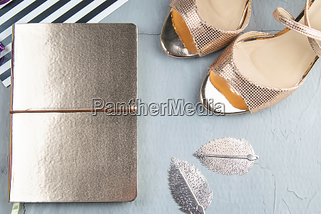 a gold notebook with womens shoes