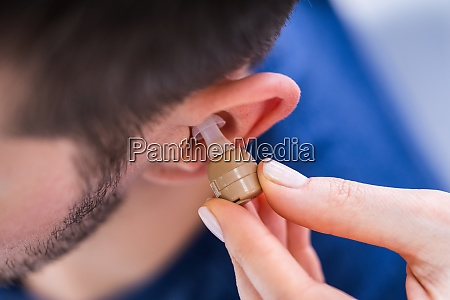 doctor inserting hearing aid in mans