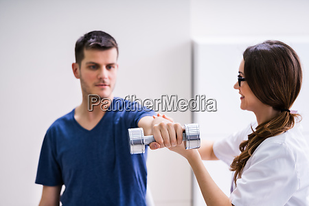 therapist assisting male patient while doing