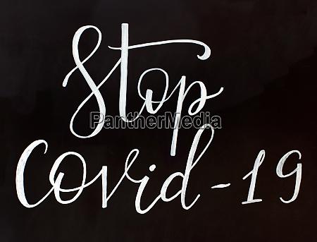 chalk inscription stop covid 19 on