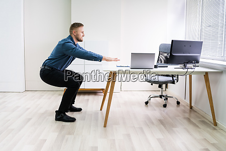 smiling young businessman doing sit ups