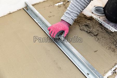 construction worker aligns concrete screed floor